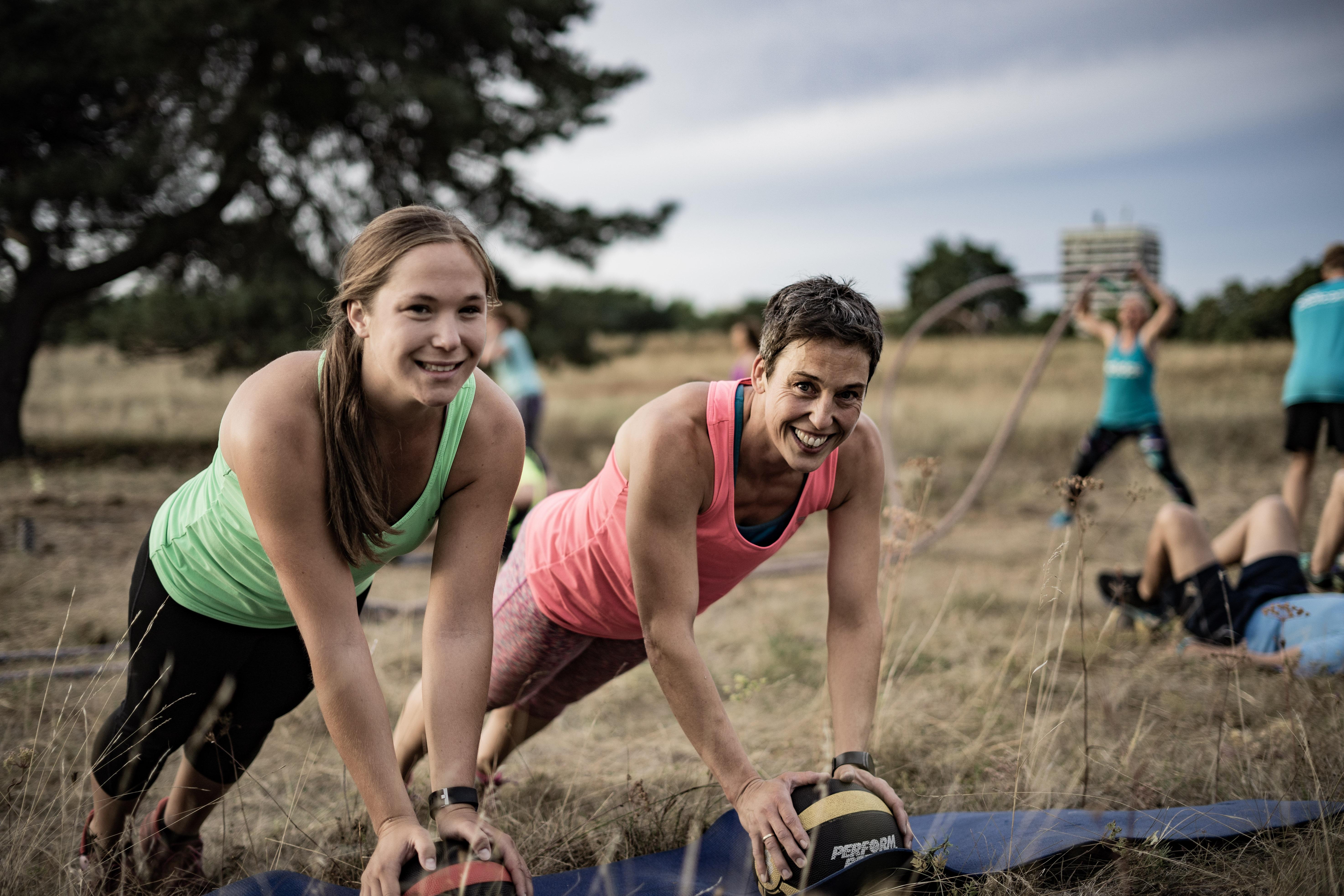 Frauen beim Training mit Medizinbällen beim bootcamp outdoor